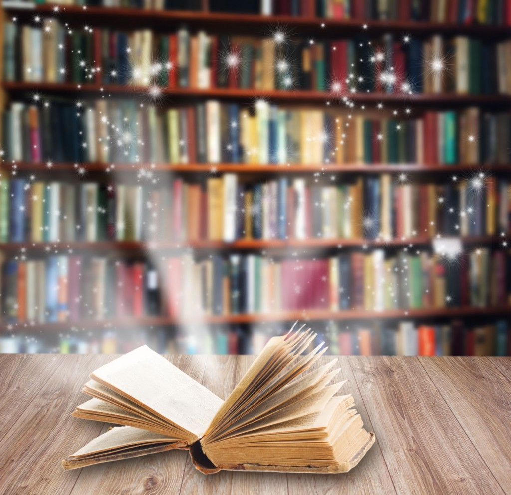 43267907 - open book on wooden book shelf with magic light